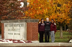 Students pose beside Eastern Kentucky University entrance sign