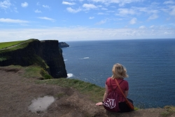 Shelby Fain sitting on the edge of the Cliffs of Moher in County Clare, Ireland