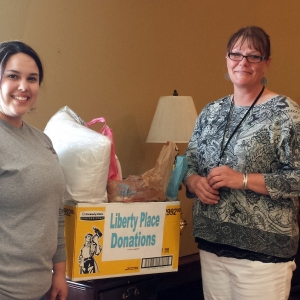 Bianca Robles presents Shanna Wells with donated items